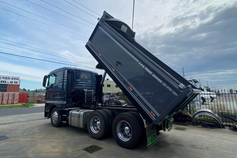 Rear view of grey paint custom tipper truck body with tipper body extended